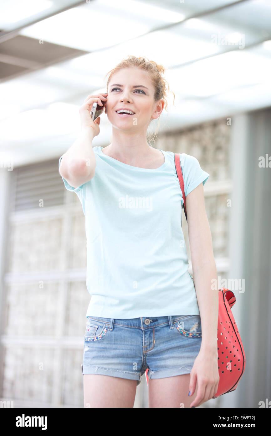 Donna felice che guarda lontano mentre si utilizza il telefono cellulare all'aperto Immagini Stock