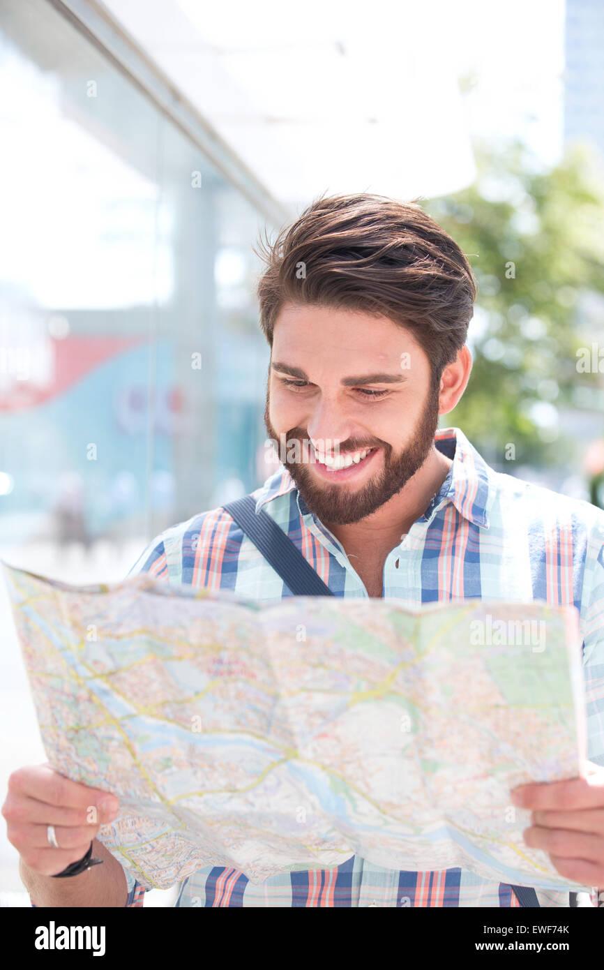 Uomo felice reading road map in città Immagini Stock