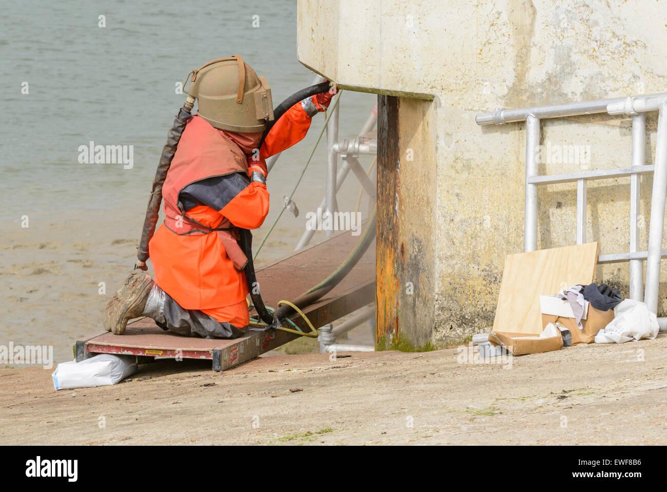 La sabbiatura. Un operaio in ginocchio indossare indumenti di protezione durante la sabbiatura. Immagini Stock