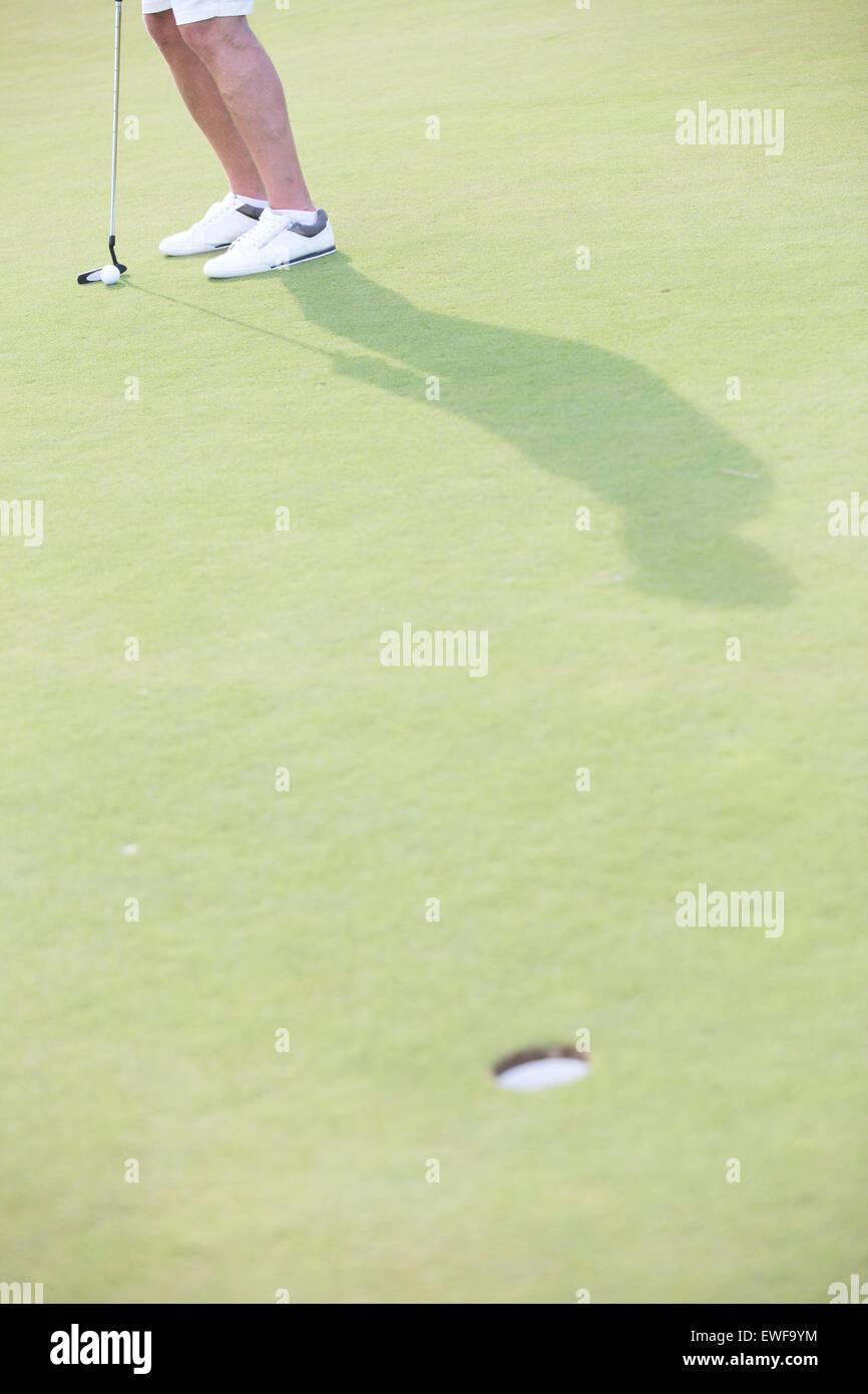 Sezione bassa di uomo di mezza età giocare a golf in corso Immagini Stock