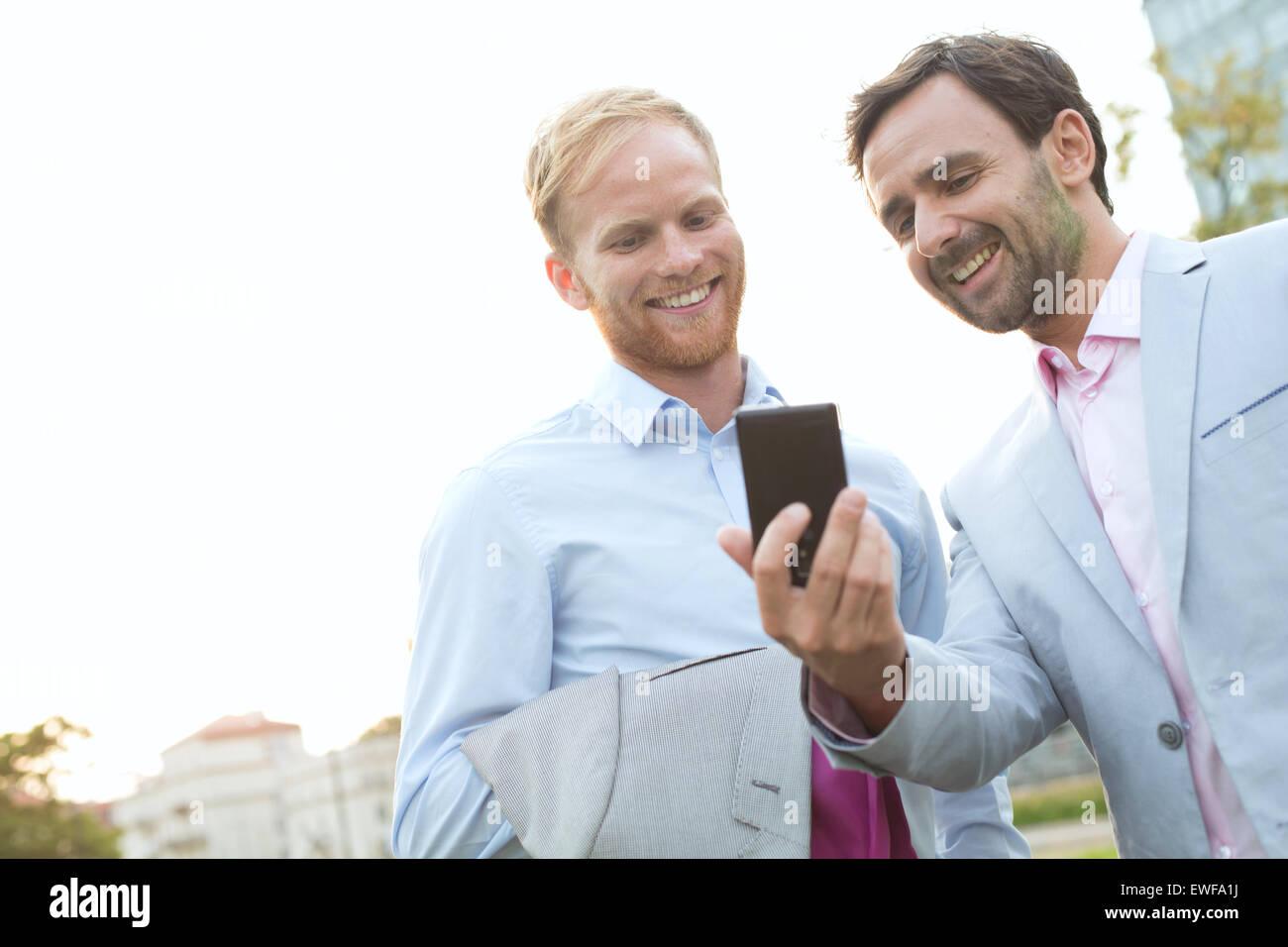 Imprenditori tramite telefono cellulare contro il cielo chiaro Immagini Stock