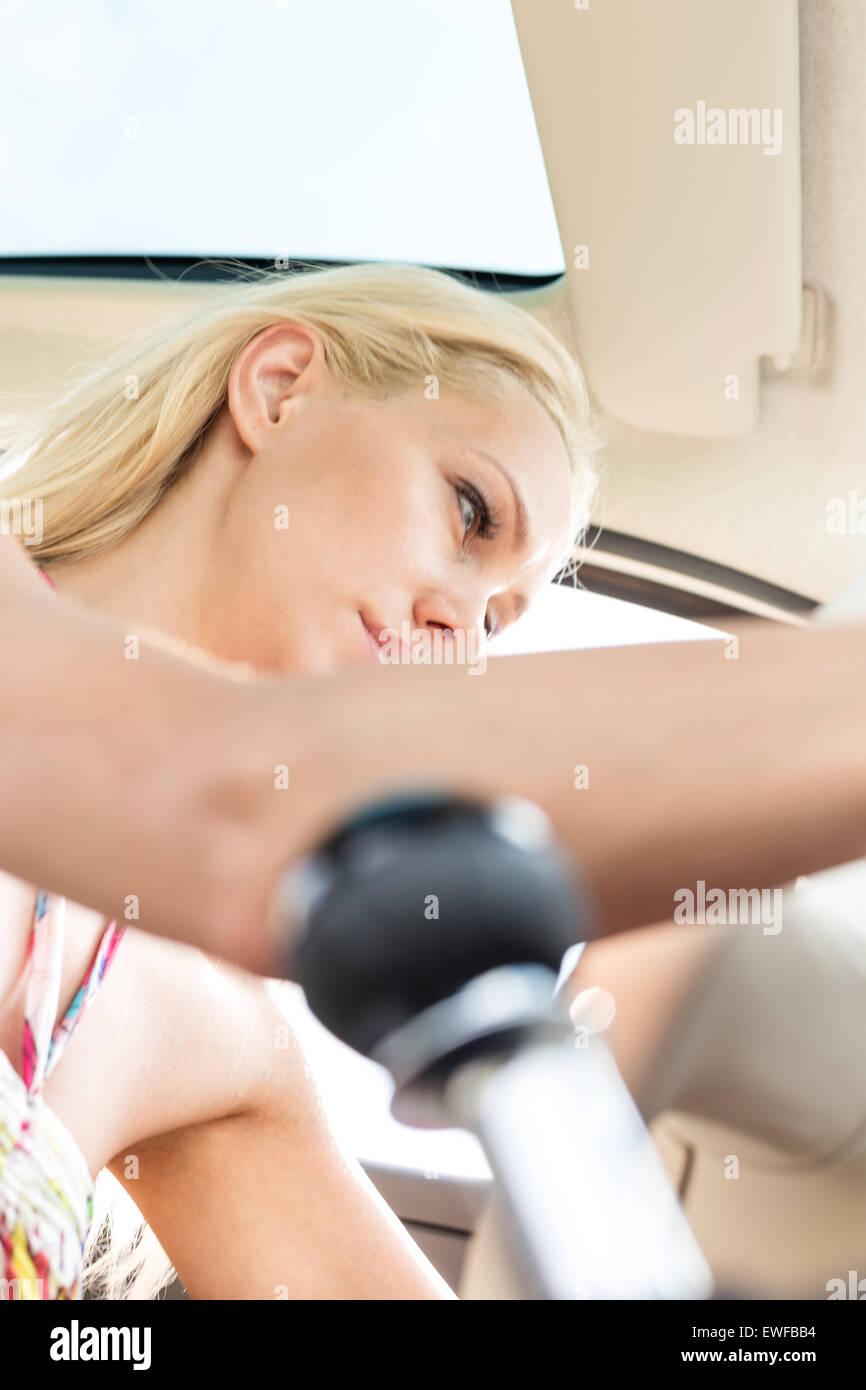 Basso angolo di visione della donna seduta in auto Immagini Stock