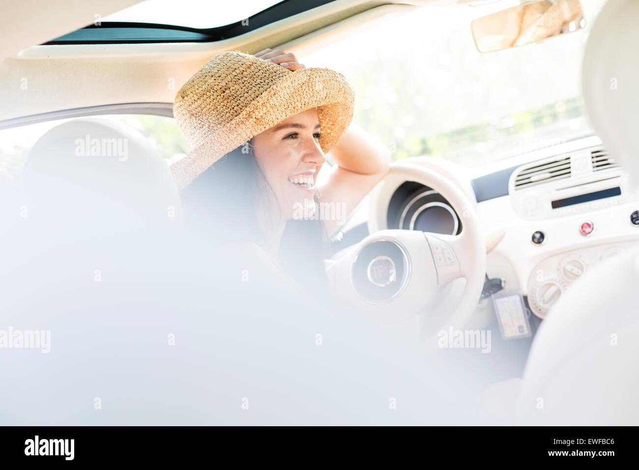 Felice donna seduta in auto Immagini Stock