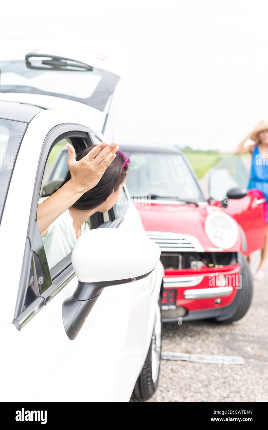 Arrabbiato donna gesticolando mentre parla a femmina di schiantarsi auto sulla strada Immagini Stock