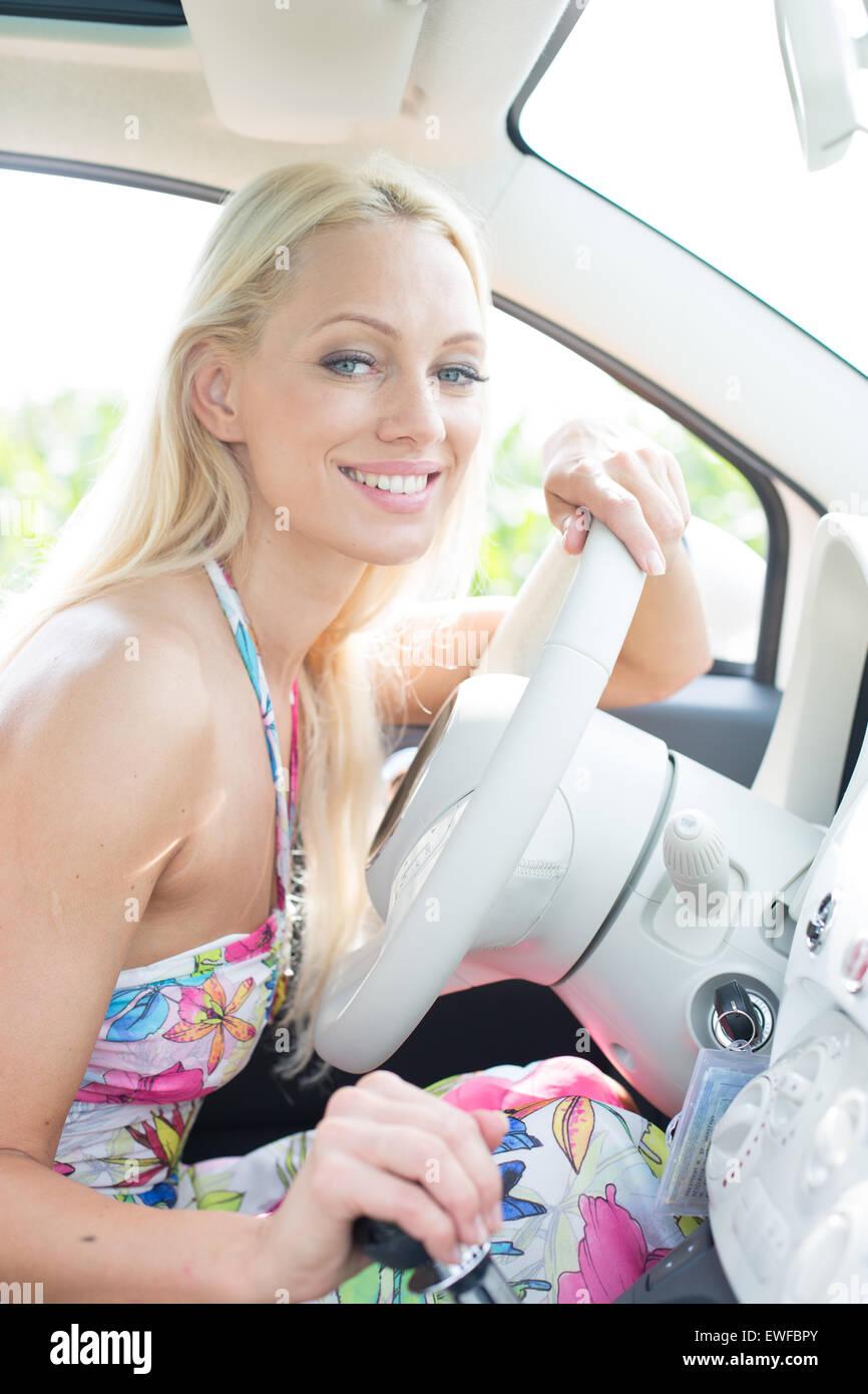 Ritratto di donna felice seduta in auto Immagini Stock