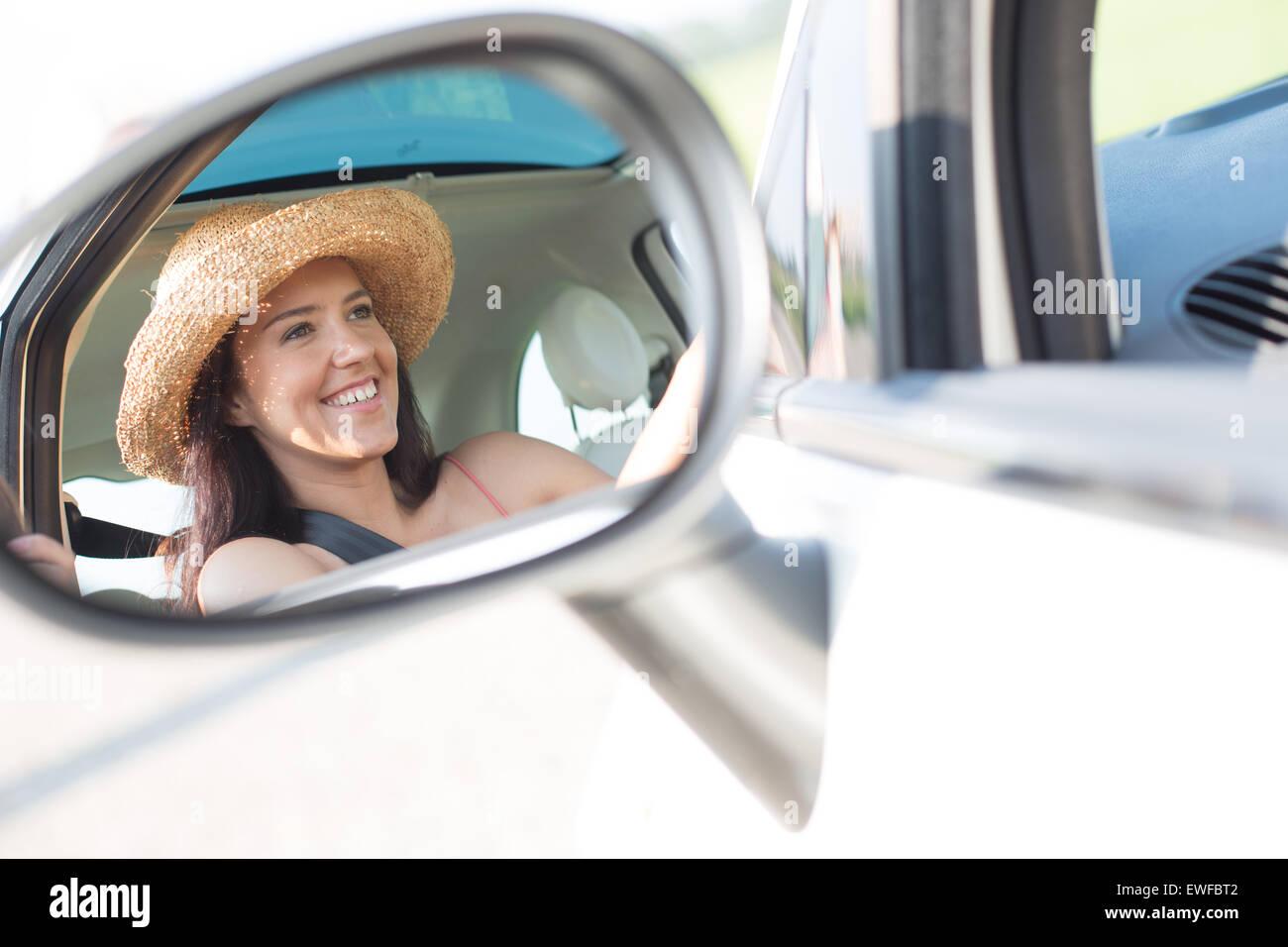 La riflessione di donna felice in specchietto retrovisore della macchina Immagini Stock