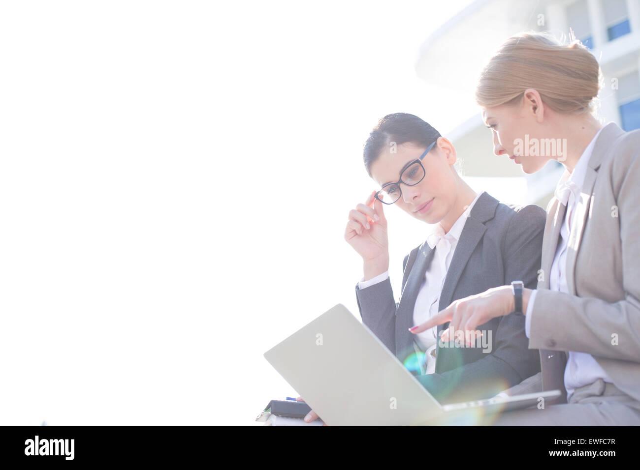 Basso angolo vista di imprenditrici utilizzando laptop contro il cielo chiaro Immagini Stock