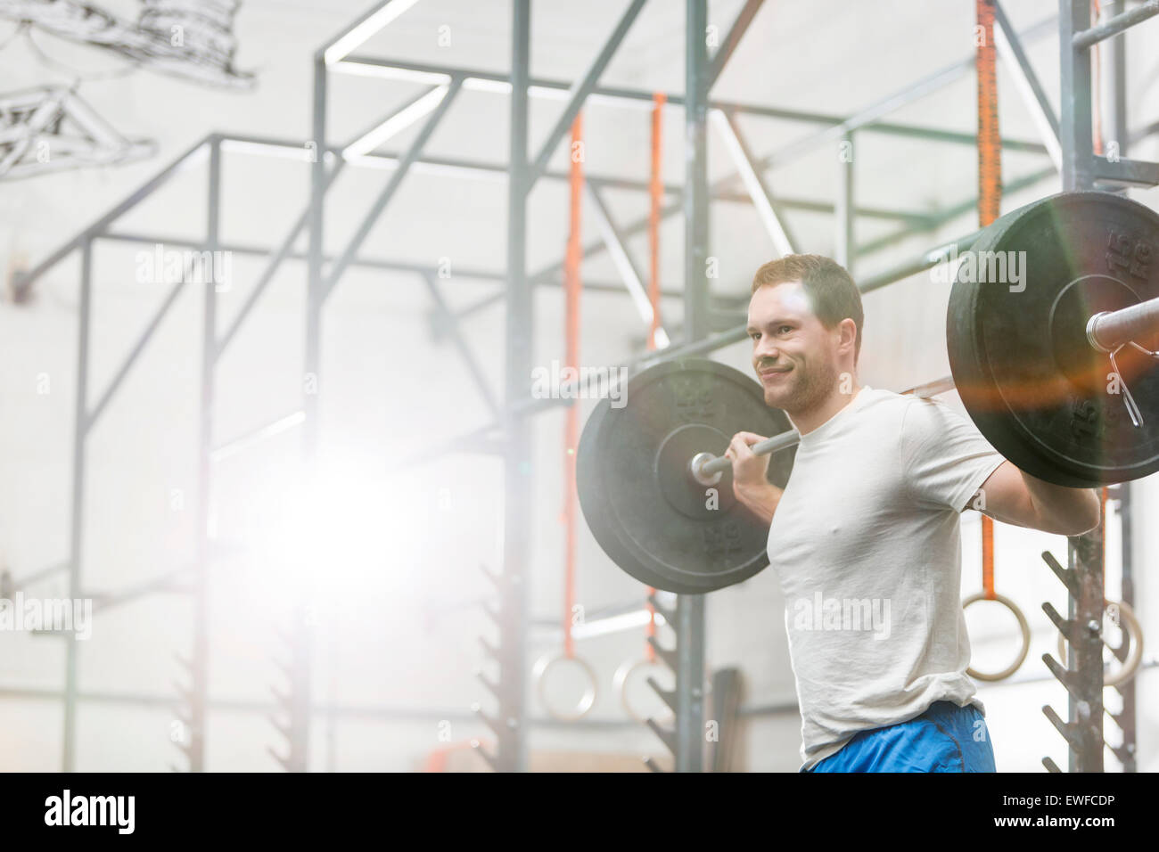 Uomo sorridente il sollevamento barbell in palestra crossfit Foto Stock