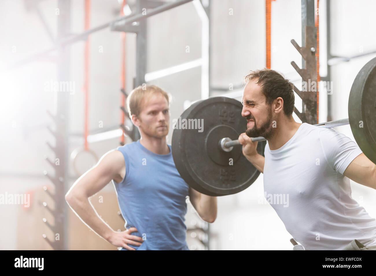 L'uomo aiutando un amico in sollevamento barbell in palestra crossfit Immagini Stock