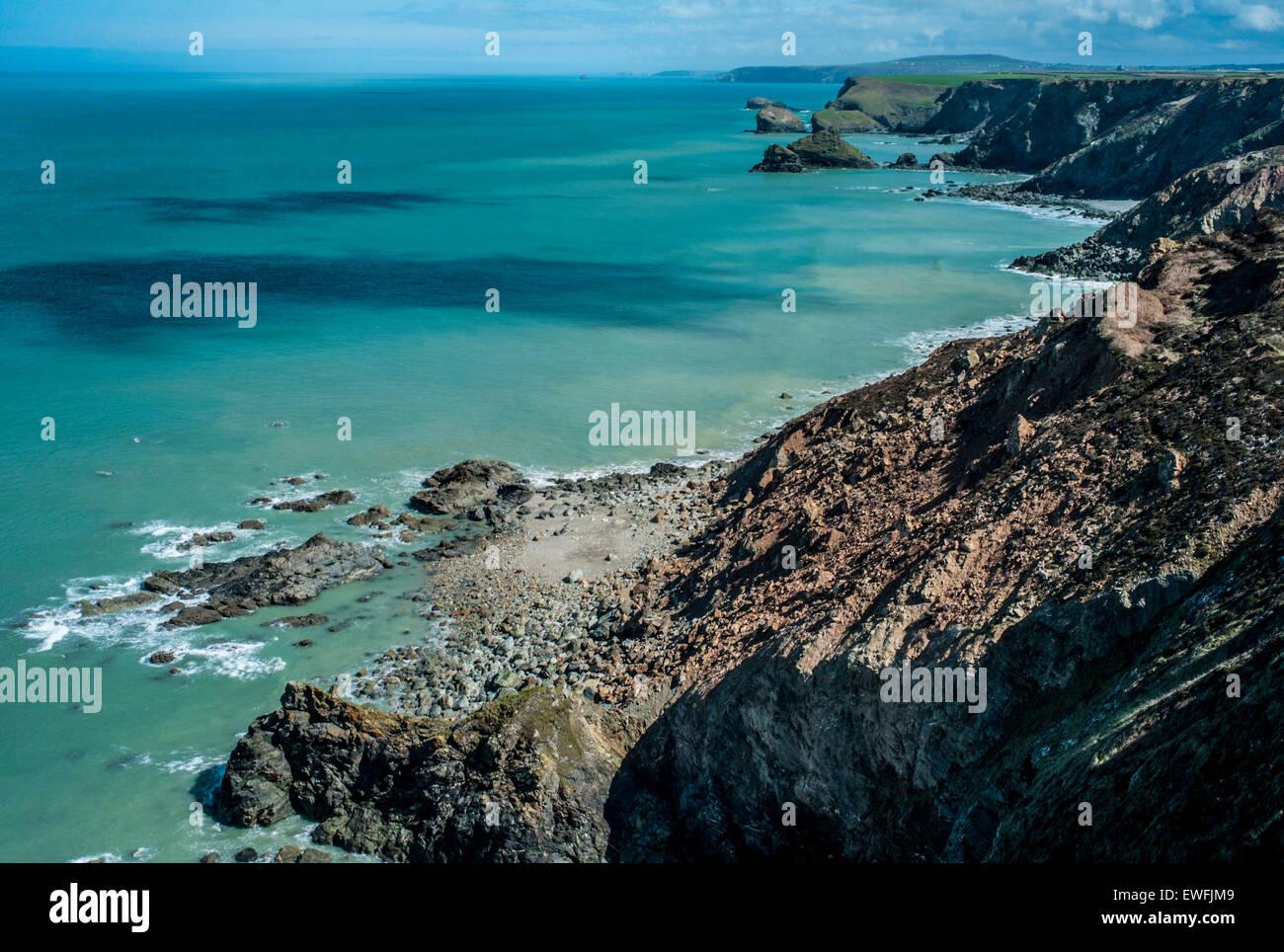 Un turquise oceano con ombre sulla superficie e una vista di una costa rocciosa del paesaggio. Immagini Stock
