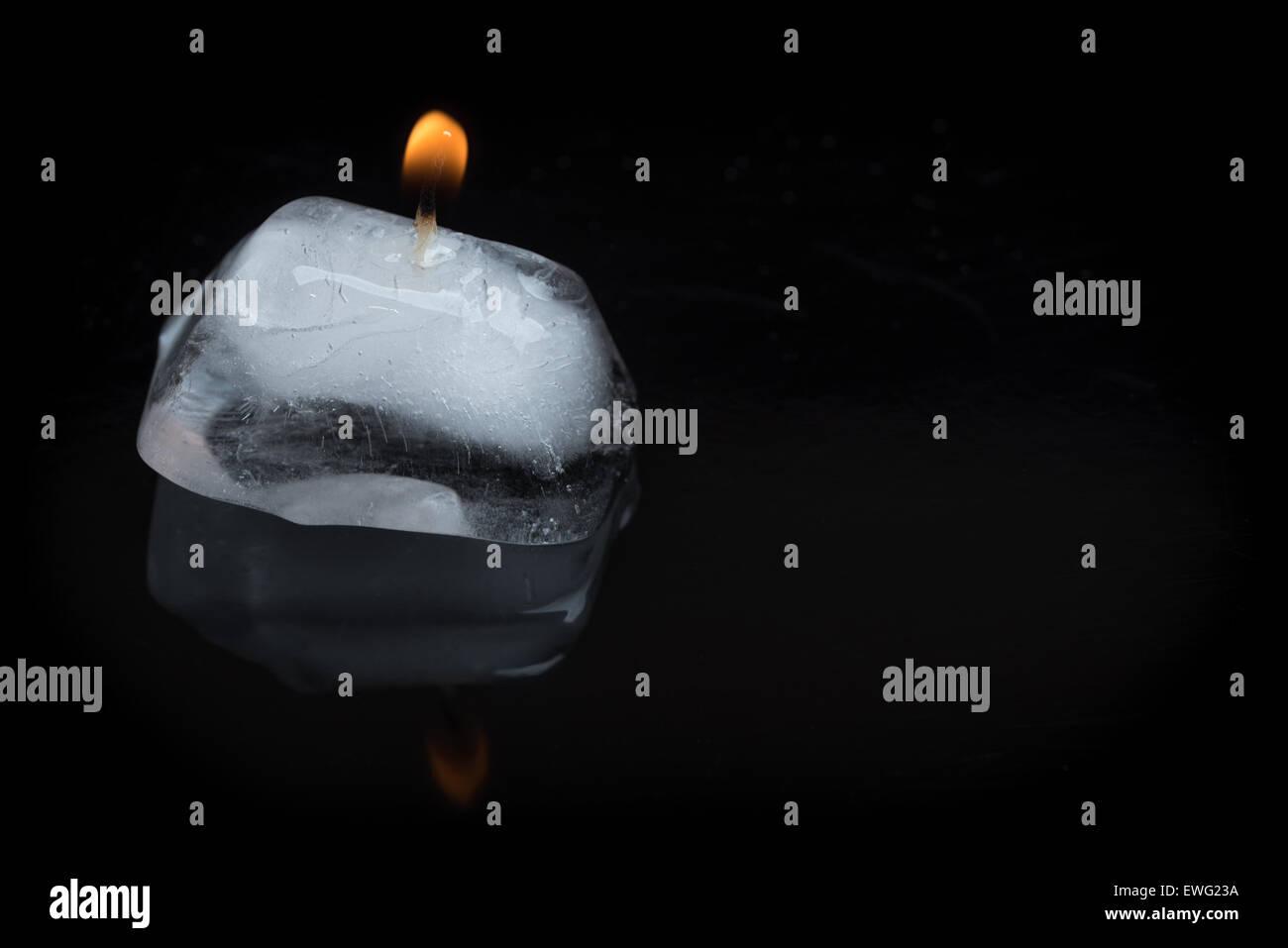Un'immagine ravvicinata di una candela accesa stoppino bloccato in un cubo di ghiaccio su uno sfondo nero con Immagini Stock