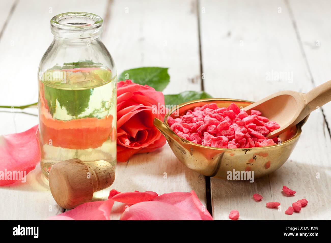 Ancora in vita con sale da bagno, essenza e rosa rosa su sfondo rustico Immagini Stock