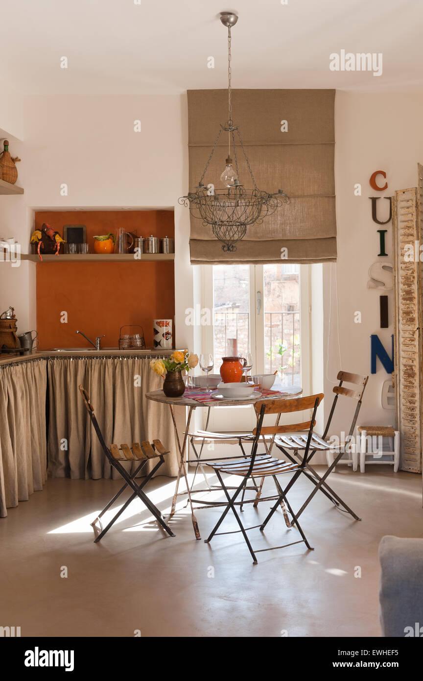 Filo francese lampadario sopra café tavolo e sedie in cucina rustica ...