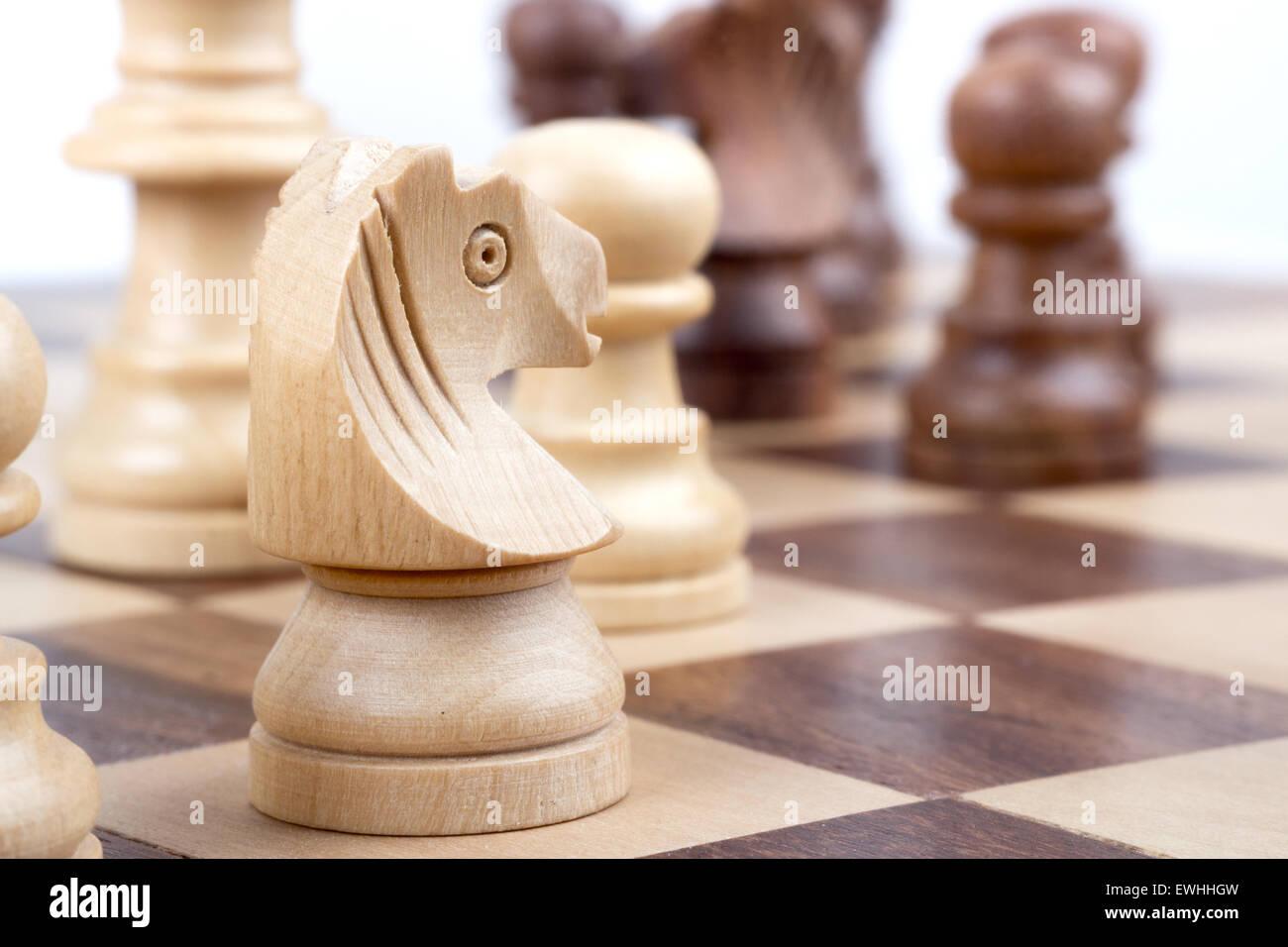 Pezzi di scacchi nel corso di una scacchiera. Immagini Stock