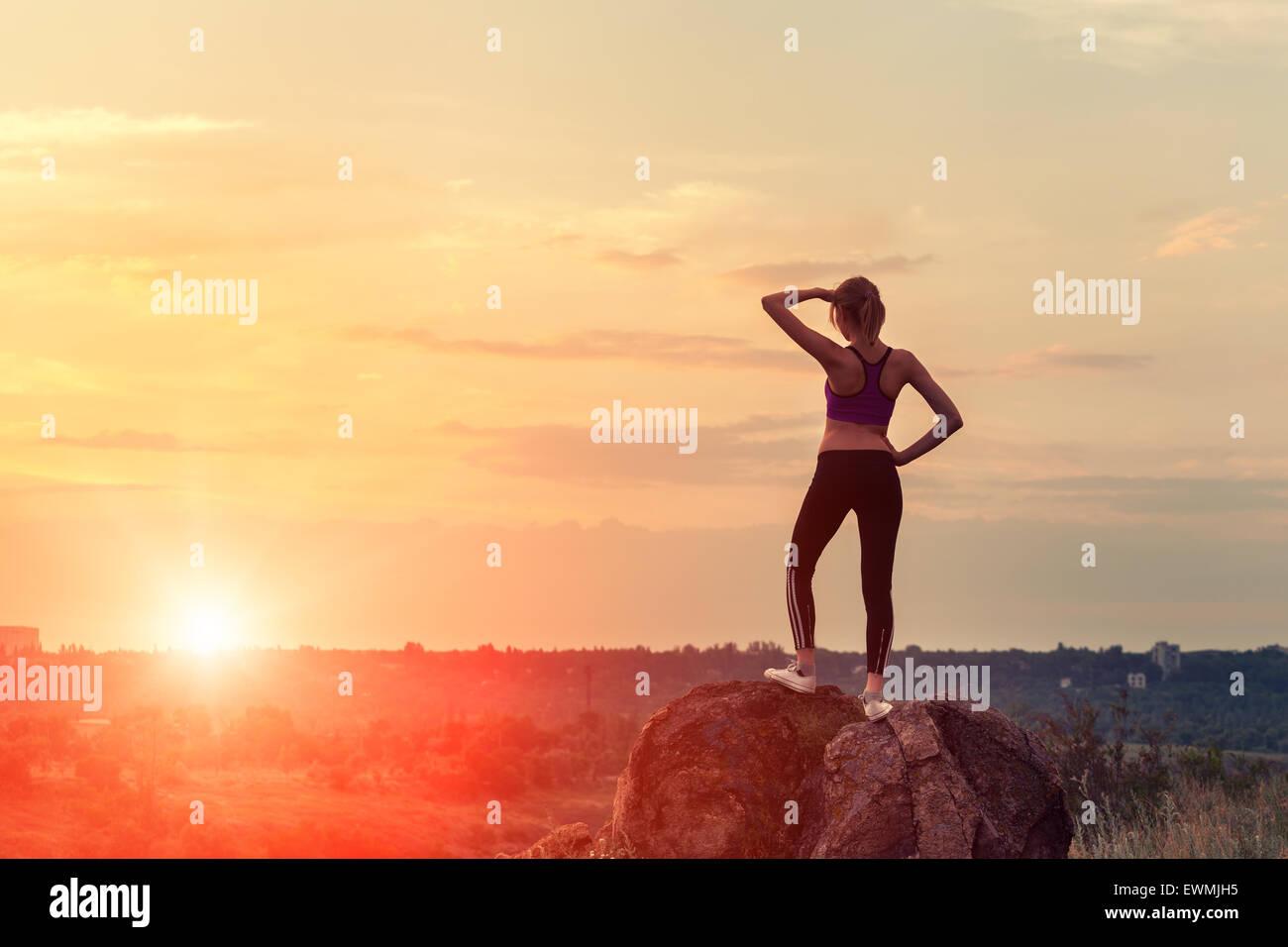 Giovane donna sportivo con le braccia sollevate fino al tramonto in estate Immagini Stock