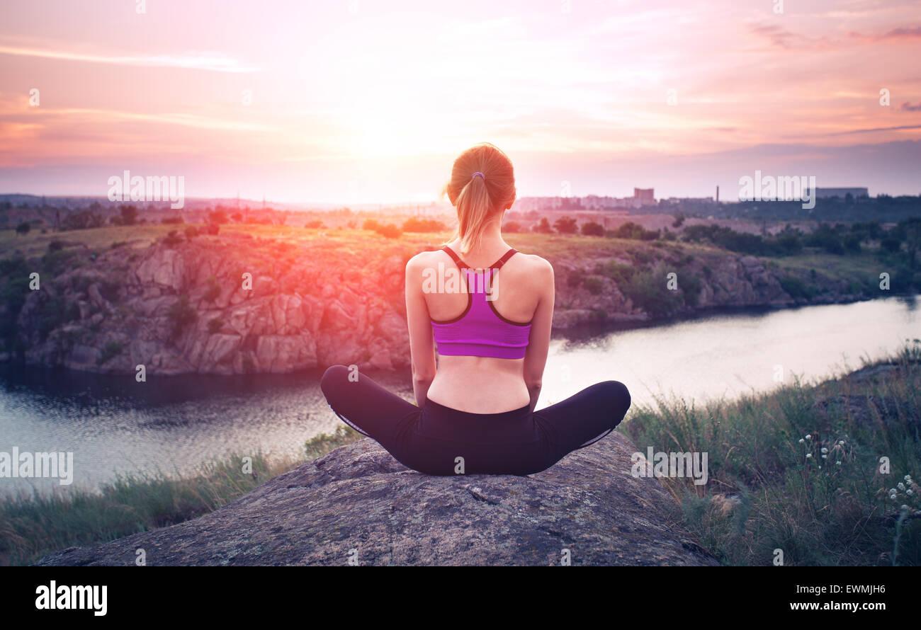 Giovane donna a praticare yoga sulla collina al tramonto vicino al fiume. Immagini Stock