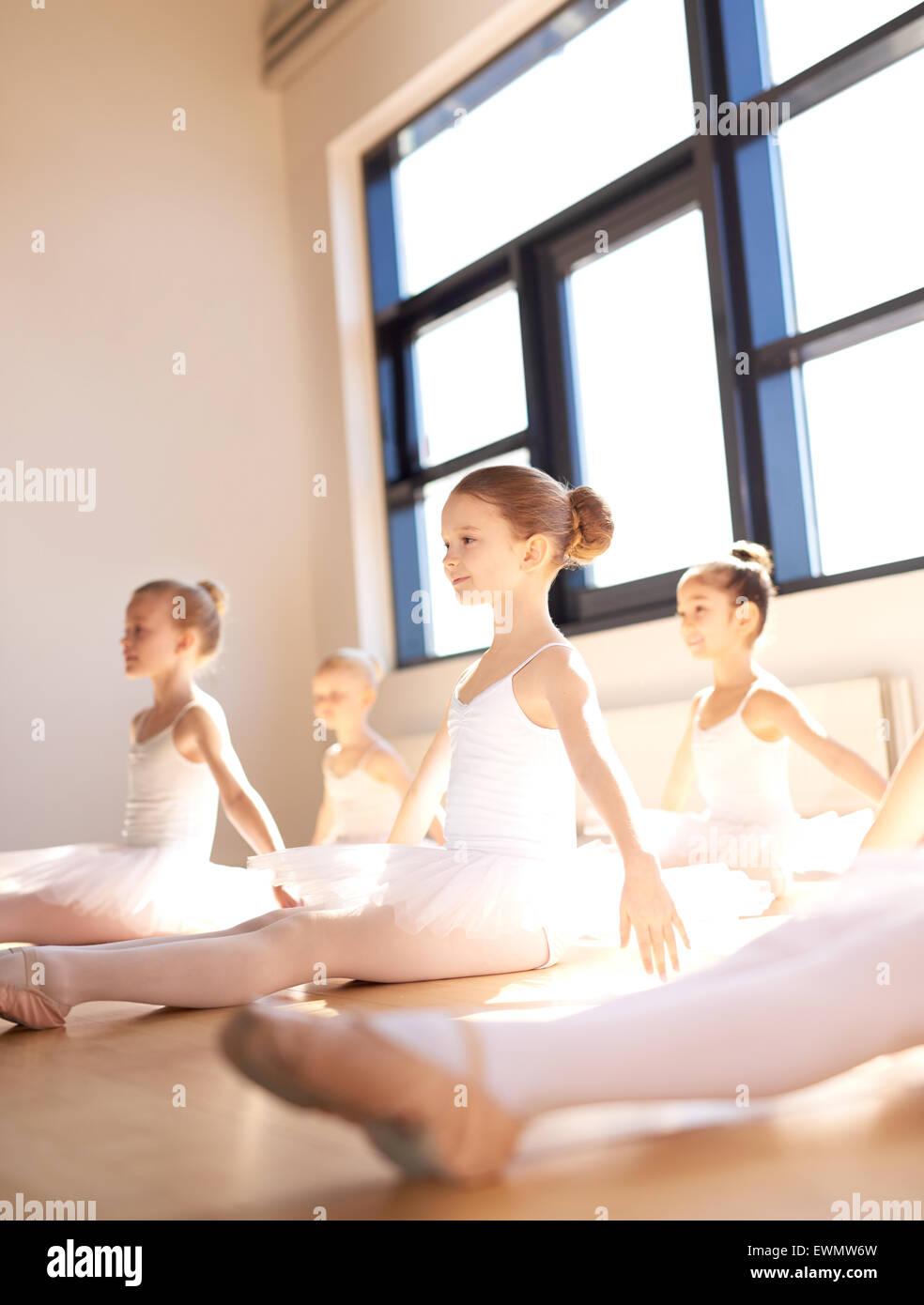Classe di giovani ballerine praticando insieme in un luminoso monolocale soleggiato seduta sul pavimento di legno Immagini Stock