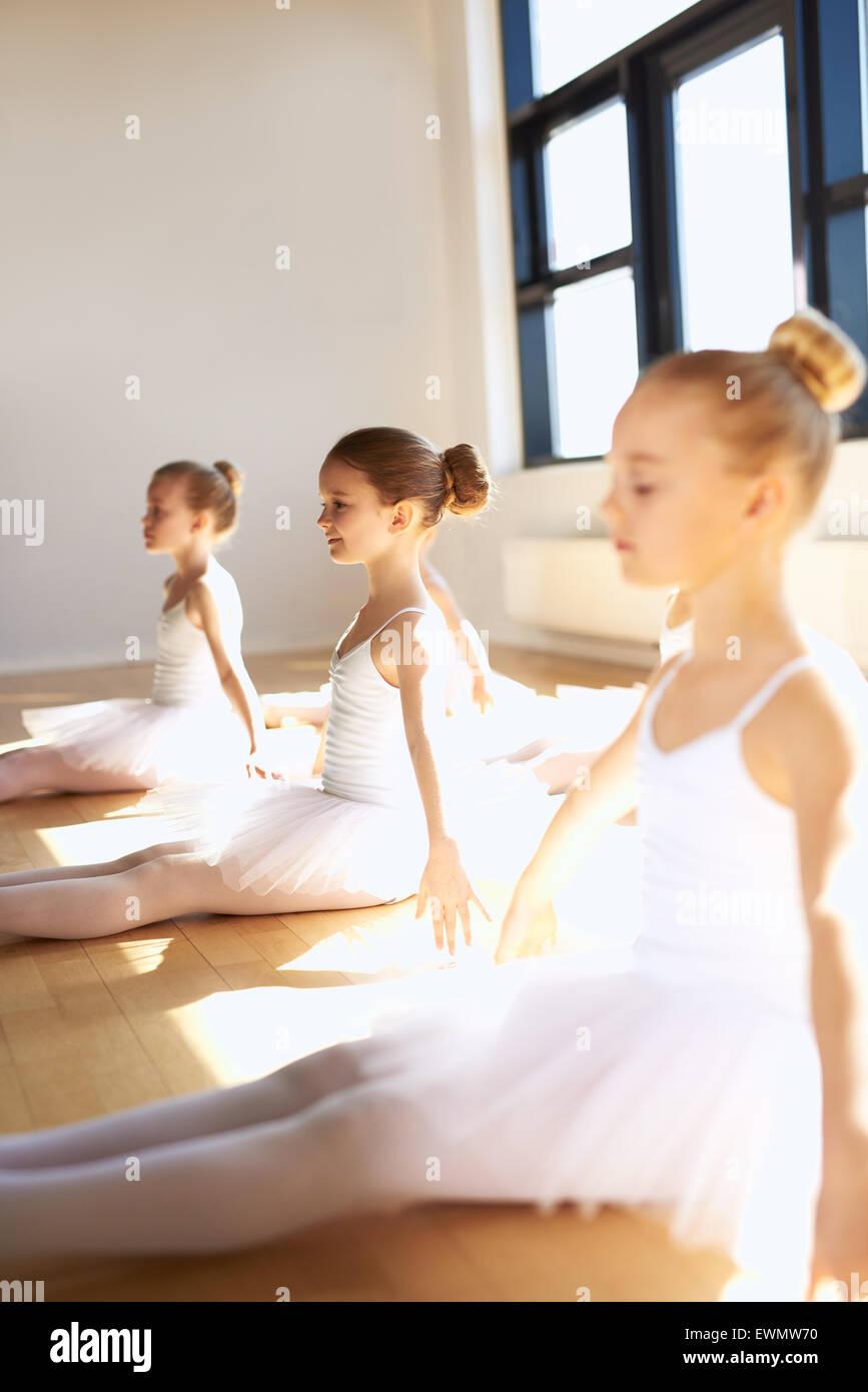 Tre giovani ragazze nelle lezioni di ballo seduti su un pavimento di legno in studio la pratica di una posa nel Immagini Stock