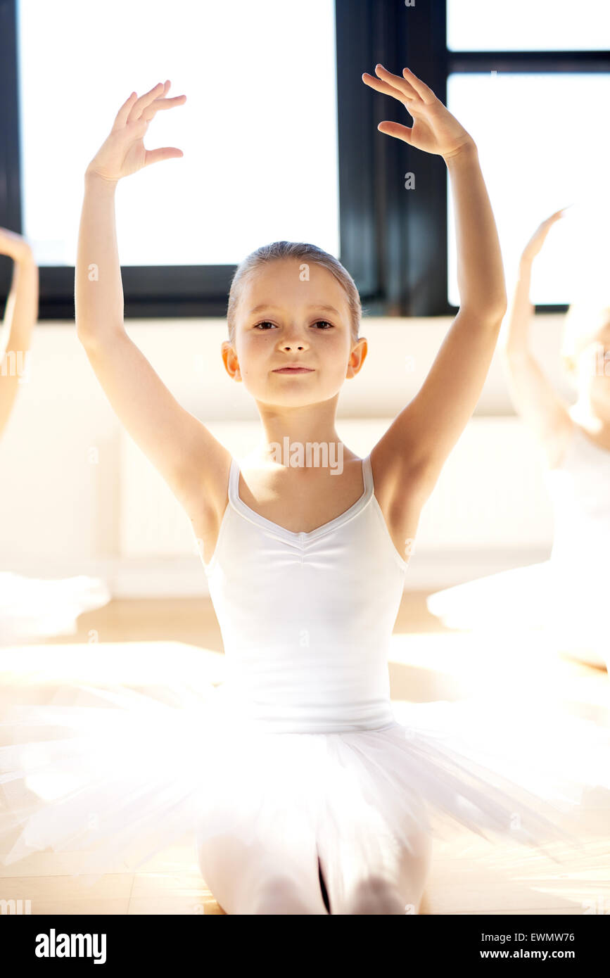 Grazioso pretty little ballerina in posa con i bracci sollevati nel suo bianco tutu in una illuminata dal sole studio Immagini Stock