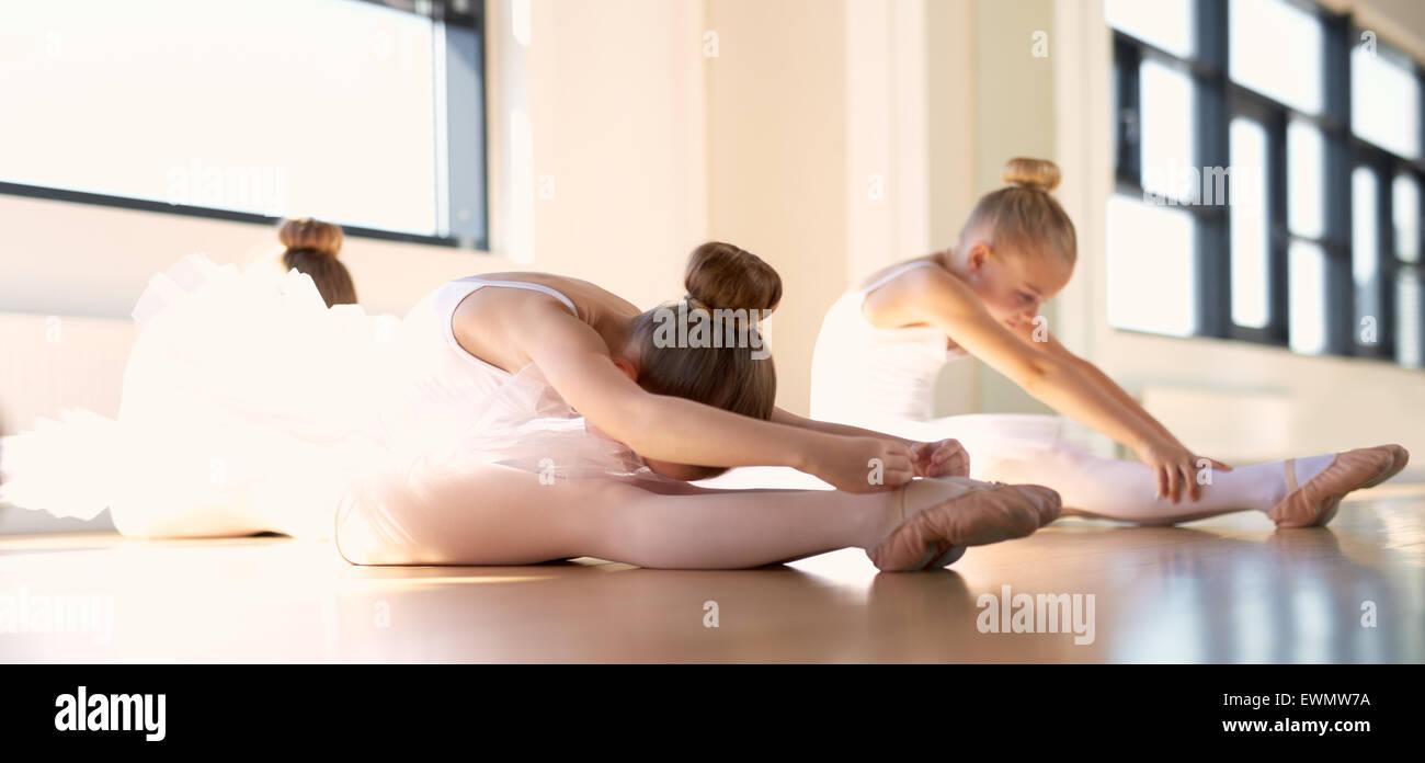 Poco balletto delle ragazze facendo stretching un esercizio di riscaldamento all'interno di Studio prima della loro Foto Stock