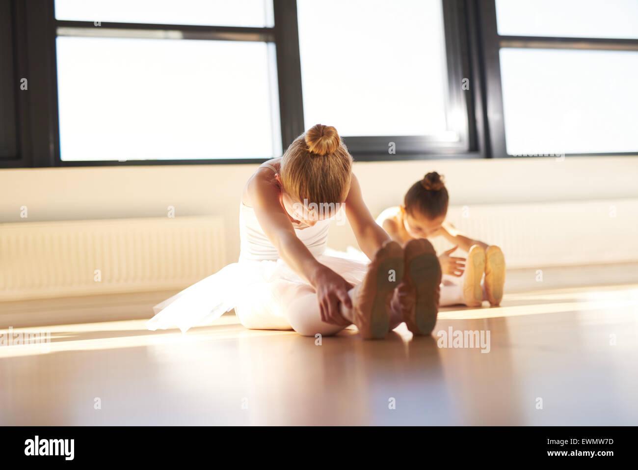 Due giovani ballerine facendo un esercizio, soprattutto per le loro gambe, all'interno dello studio prima che Immagini Stock