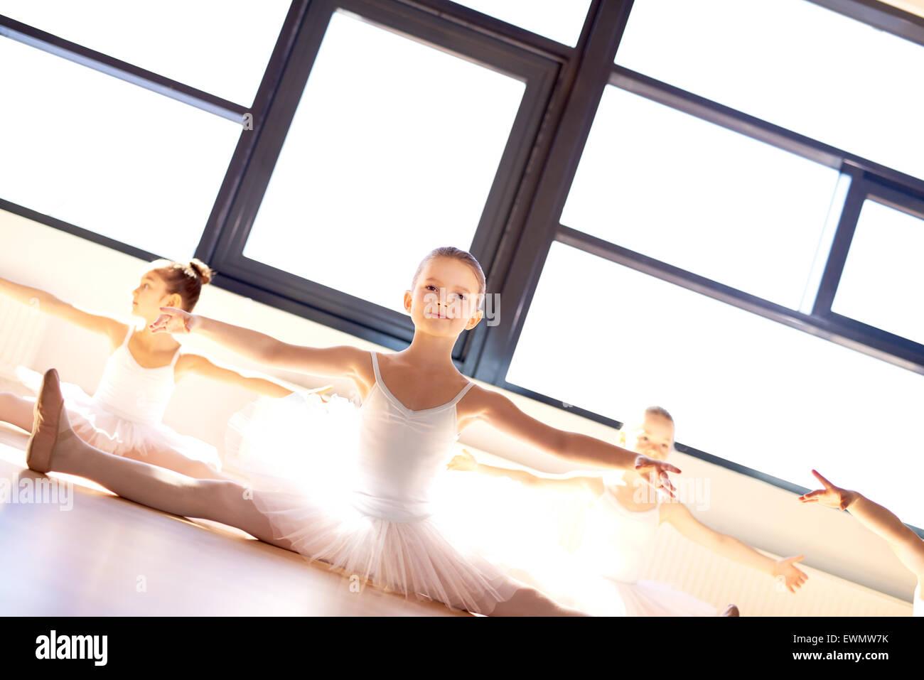Pretty little ballerina nella classe di balletto seduta sul pavimento di legno in un luminoso soleggiato dance studio Immagini Stock