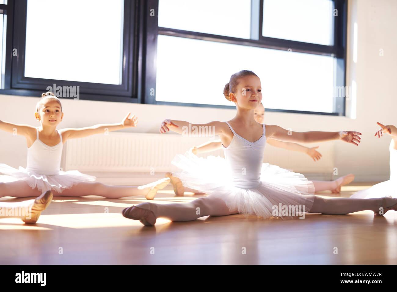Piuttosto giovani ballerini in bianco Tutus, seduto sul pavimento e stirando le braccia e le gambe come esercizio Immagini Stock