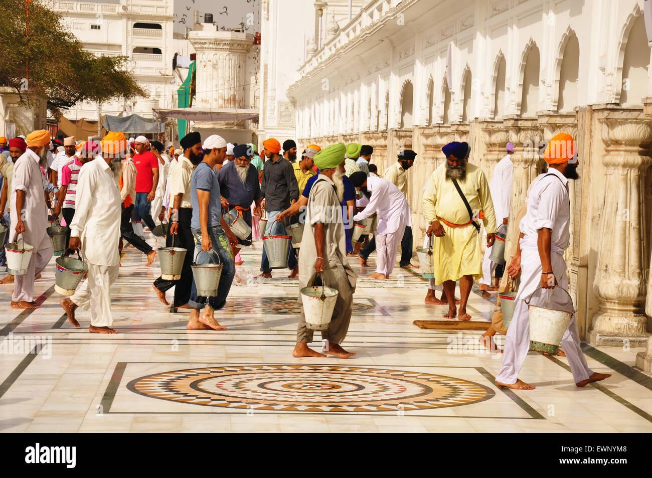 Gli uomini di religione sikh lavaggio del pavimento, Tempio Dorato, India Immagini Stock
