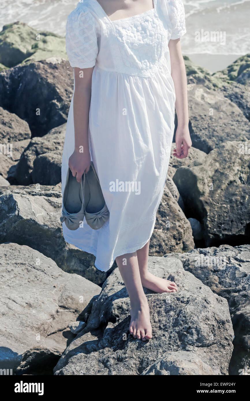 È una ragazza a piedi nudi su una roccia sul mare, tenendo le sue scarpe in mano Immagini Stock