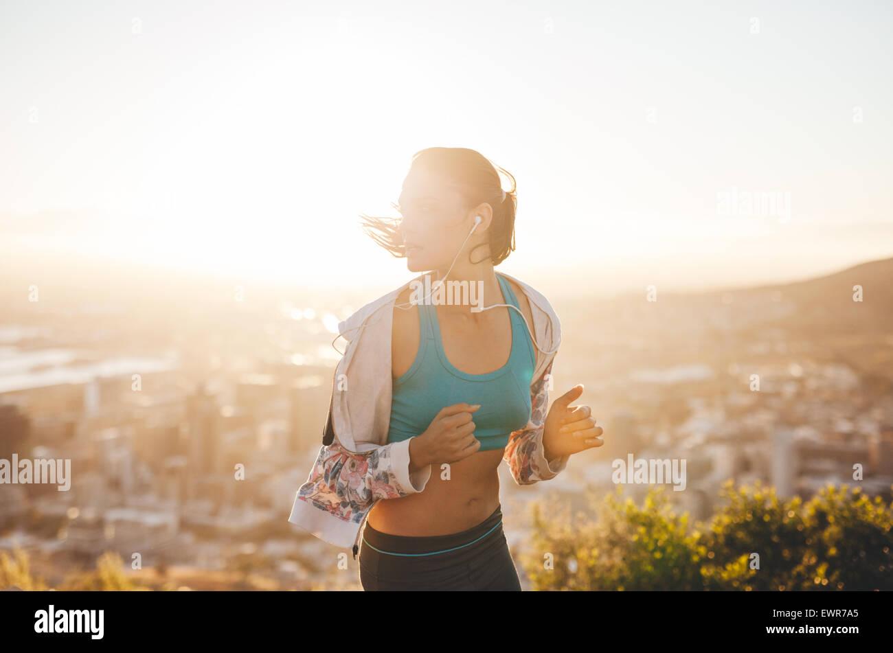 Runner di formazione nella natura con il sole che tramonta dietro di lei. Giovane donna in esecuzione all'esterno Immagini Stock