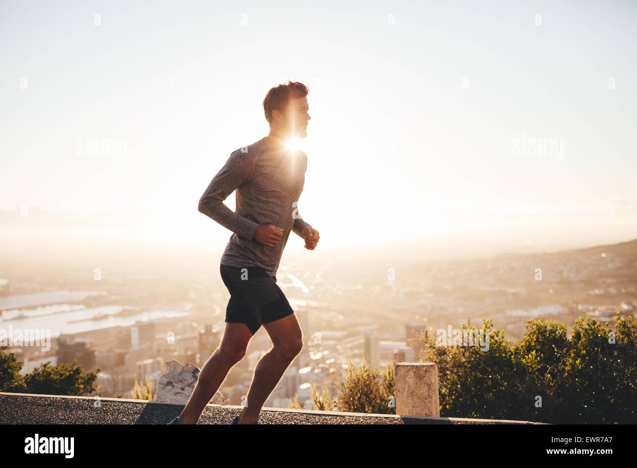 Giovane uomo di formazione nella natura con il sole che tramonta dietro di lui. Giovane uomo su run mattutino all'esterno. Immagini Stock