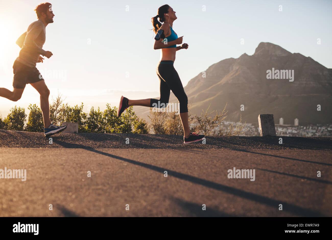 Colpo di giovane uomo e donna in corsa su strada di campagna. Coppia giovane formazione in natura. Immagini Stock
