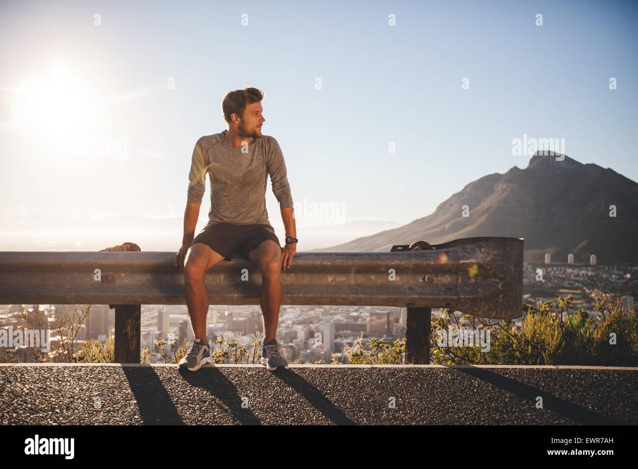 Runner maschile seduto su un guardrail sulla strada di campagna che guarda lontano sulla giornata di sole. Giovane Immagini Stock