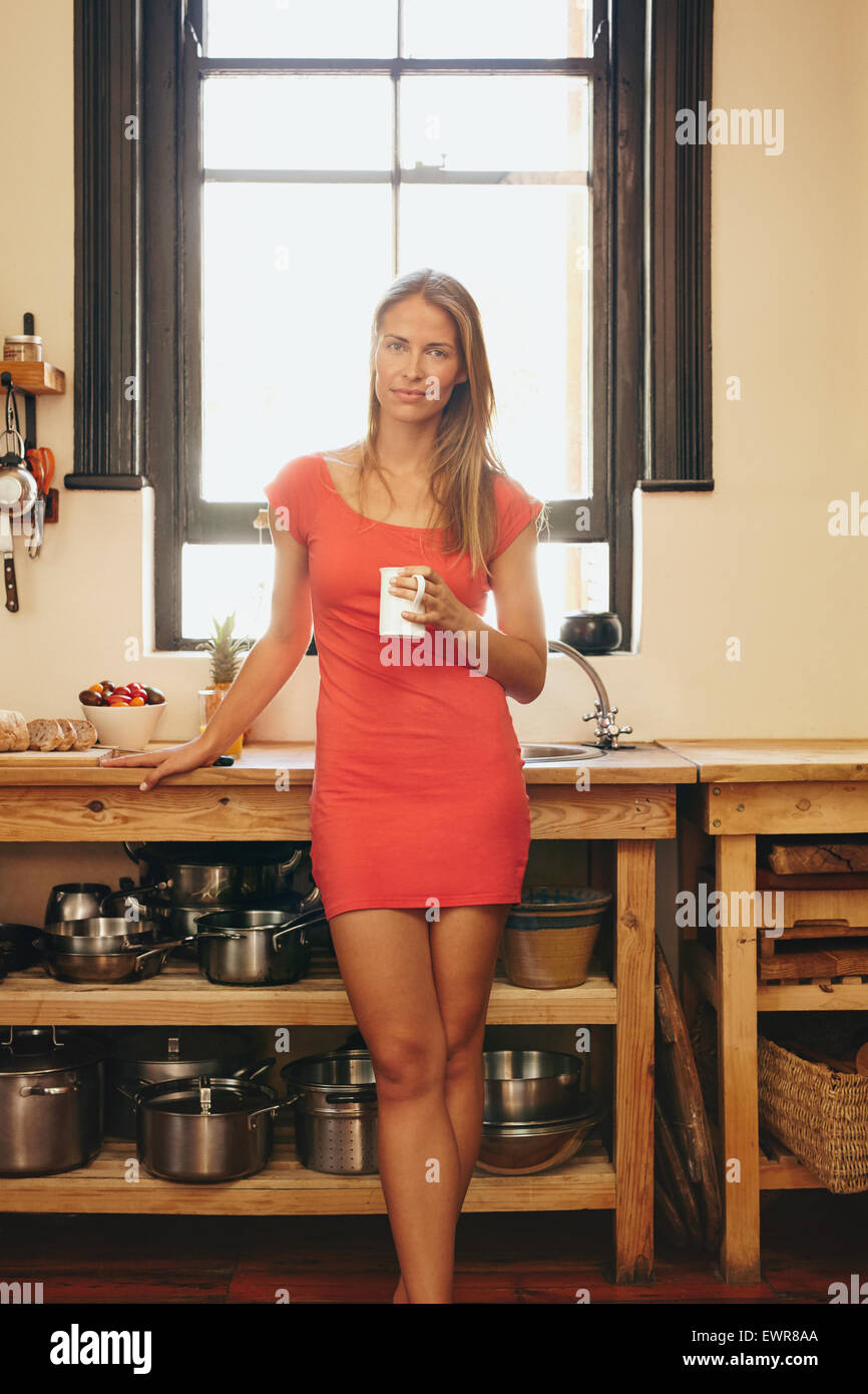Ritratto di attraente giovane donna in abito rosso in piedi in cucina tenendo una tazza di caffè. Bellissima Immagini Stock