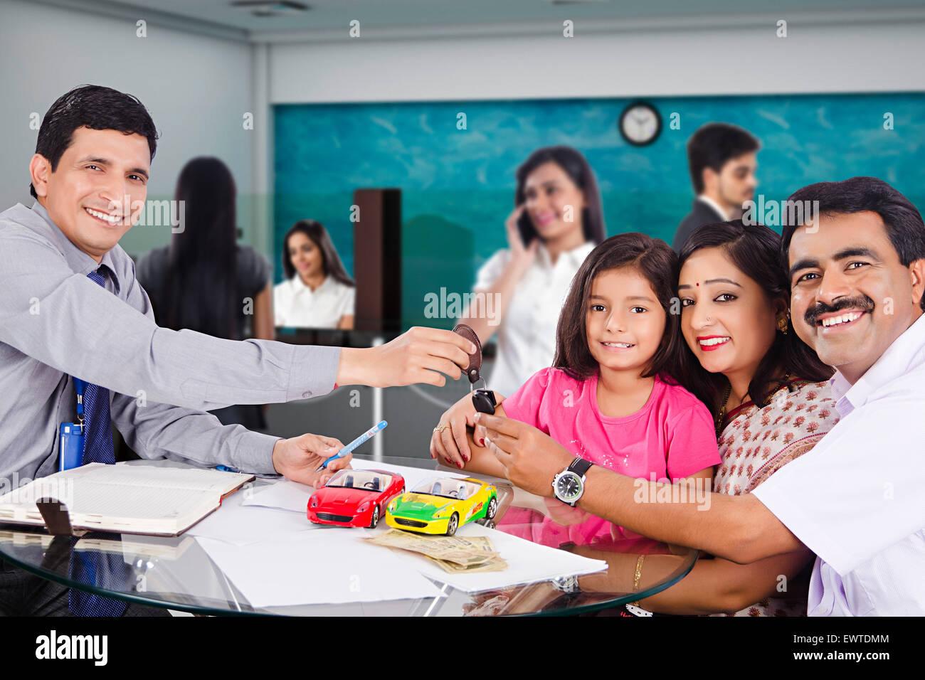 Indian genitori e addetto alle vendite di auto nuove di fronte Foto Stock