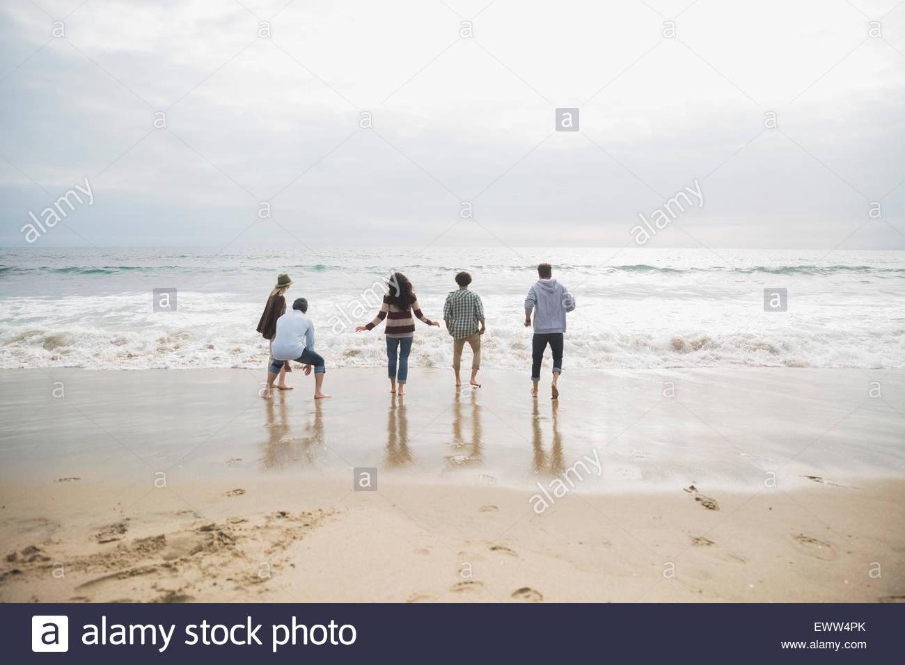 Gli amici a giocare a ocean surf in spiaggia Immagini Stock