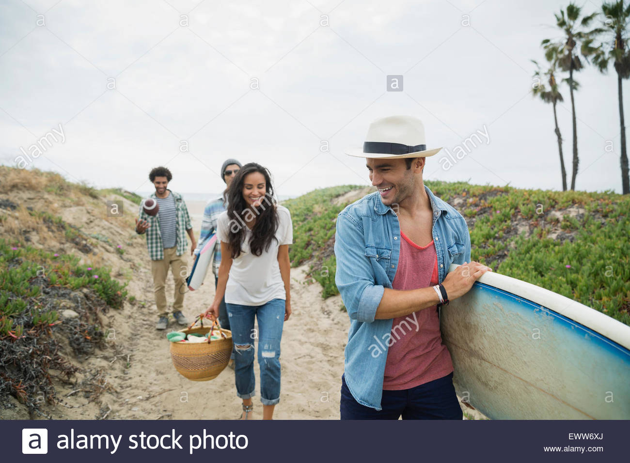Gli amici che trasportano le tavole da surf e Cesto picnic percorso spiaggia Immagini Stock