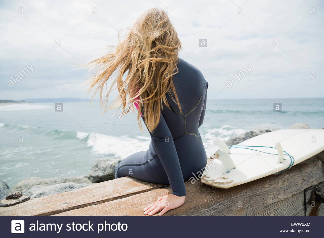 Biondo surfista femmina seduto con la tavola da surf Oceano jetty Immagini Stock