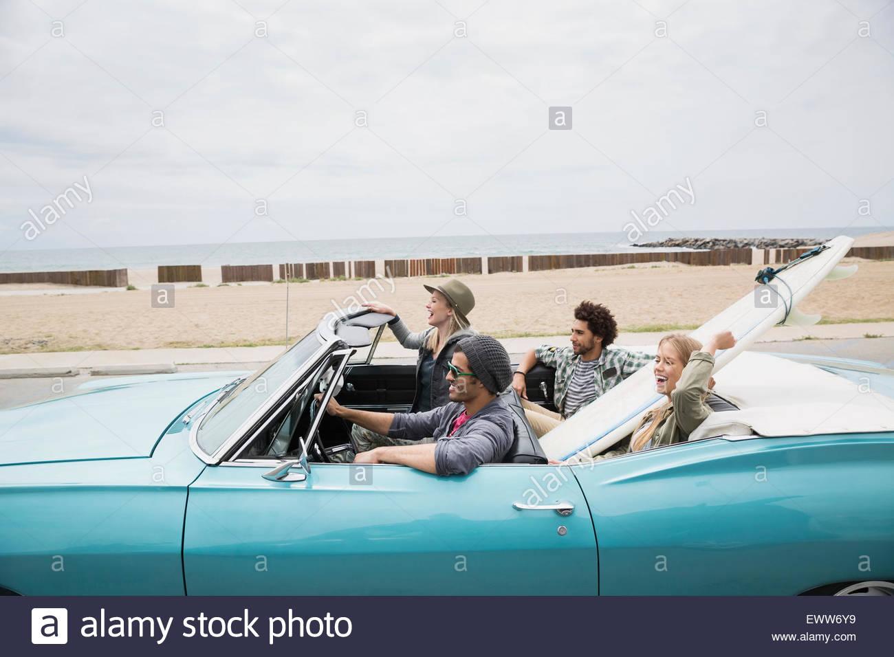 Coppie giovani a cavallo nel convertibile con tavola da surf beach Immagini Stock