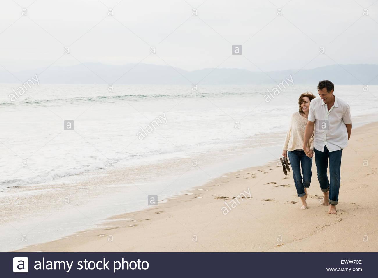 Giovane tenendo le mani e camminando sulla spiaggia Immagini Stock