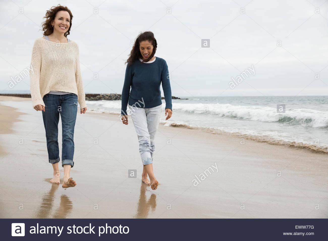 Le donne a piedi sulla spiaggia Immagini Stock