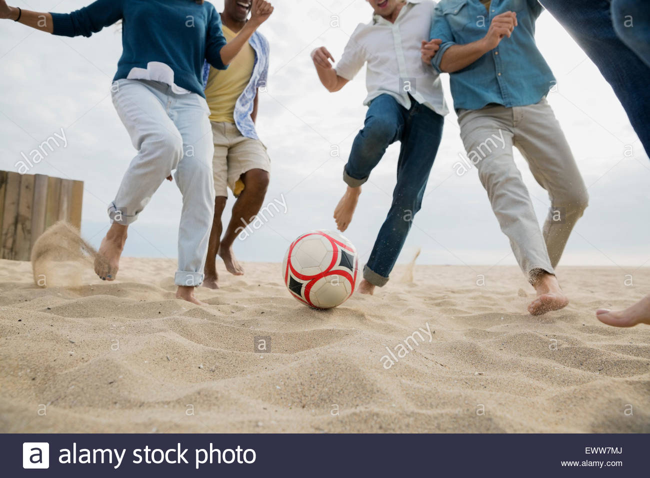 Gli amici che giocano a calcio sulla spiaggia Immagini Stock