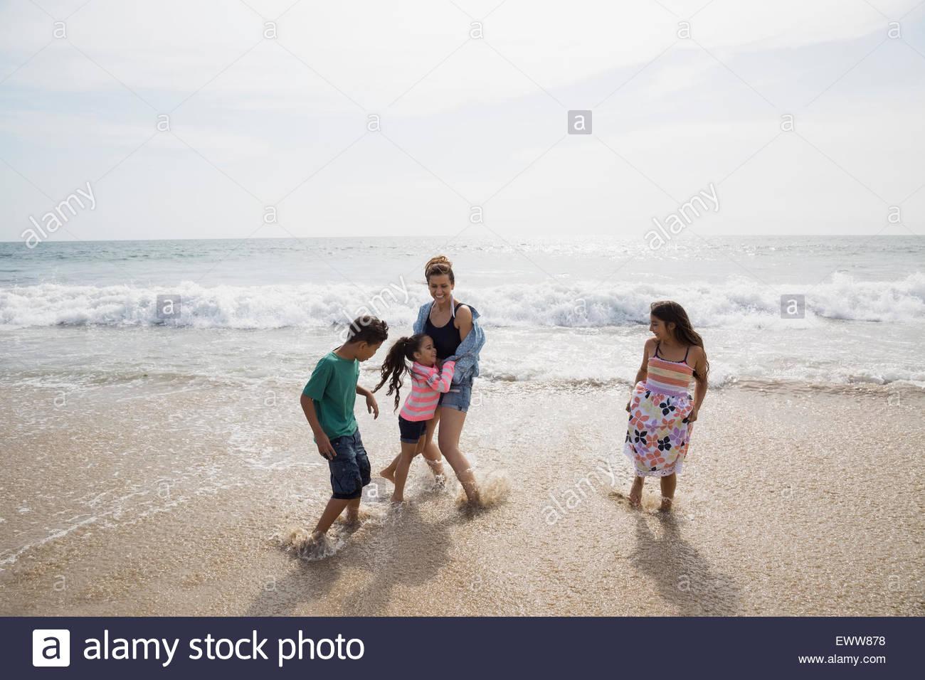 Famiglia giocando in ocean surf Immagini Stock
