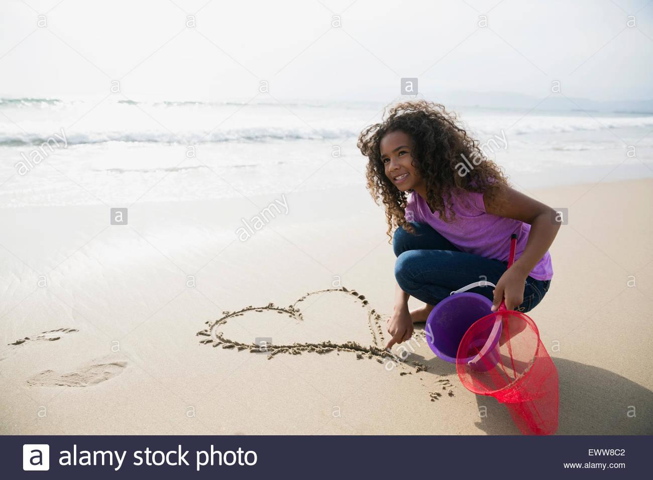 Ragazza disegno cuore-forma in sabbia sulla spiaggia Immagini Stock