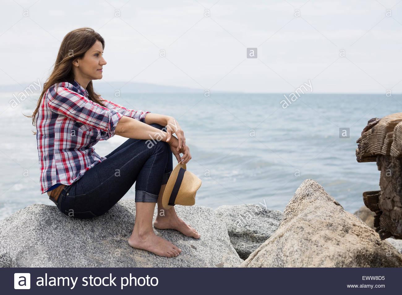 Pensieroso a piedi nudi donna seduta sulle rocce a ocean Immagini Stock