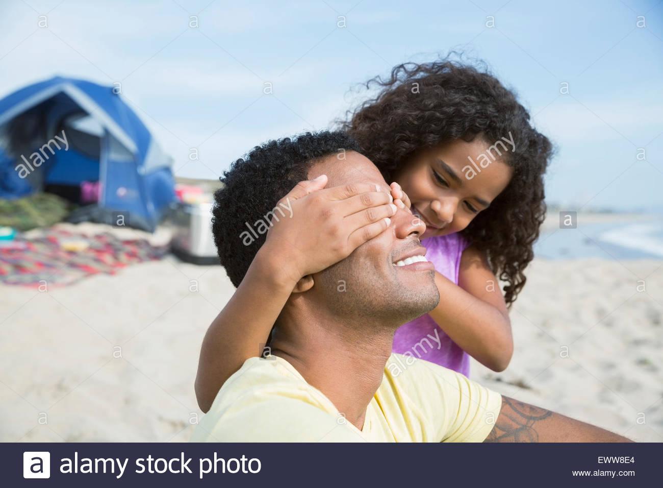 Figlia di padre di copertura gli occhi sulla spiaggia Immagini Stock