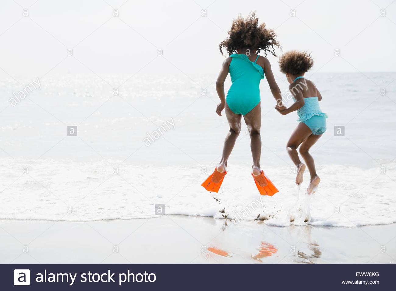Sorelle in costume da saltare in ocean surf Immagini Stock