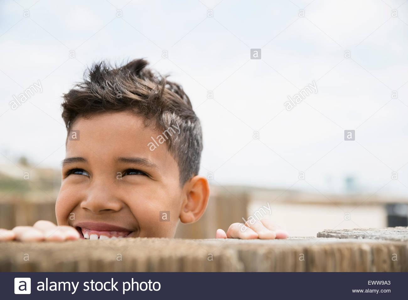 Ragazzo sorridente guardando da dietro la parete Immagini Stock