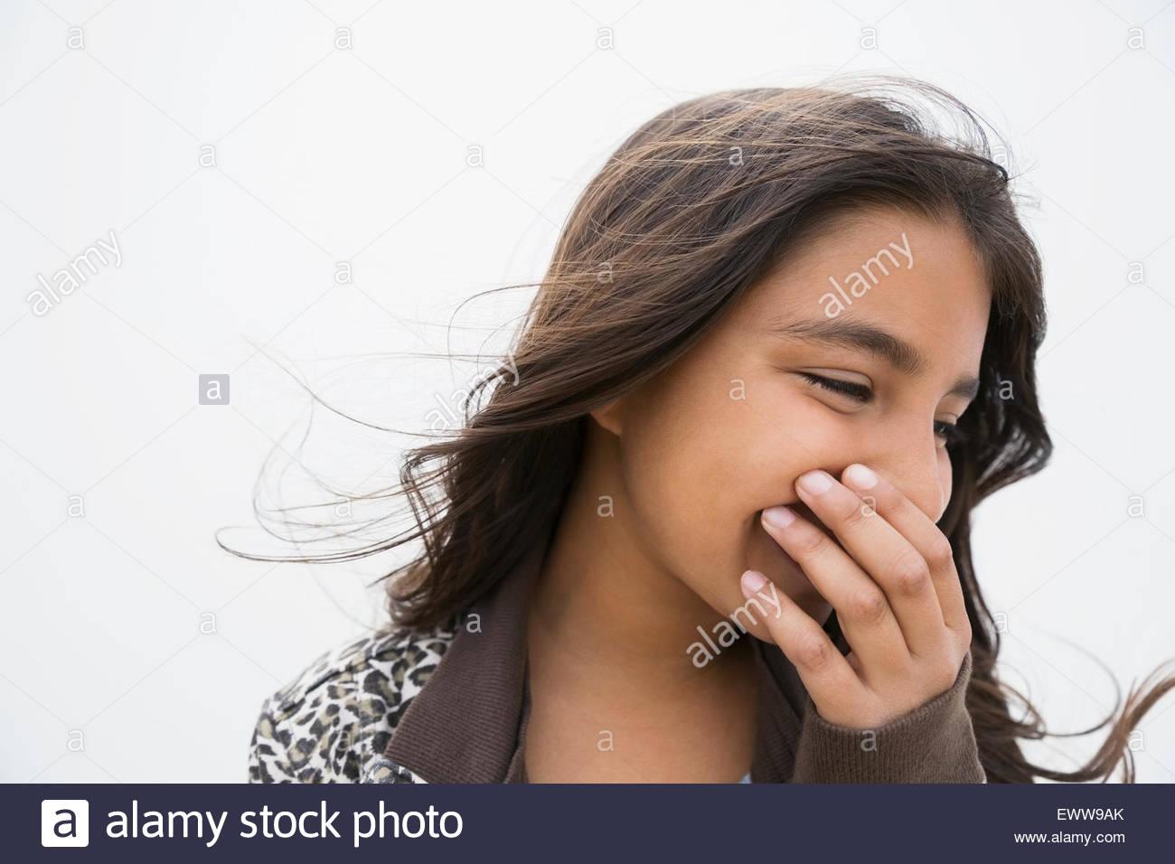 Bruna ragazza ridere che copre la bocca con la mano Immagini Stock