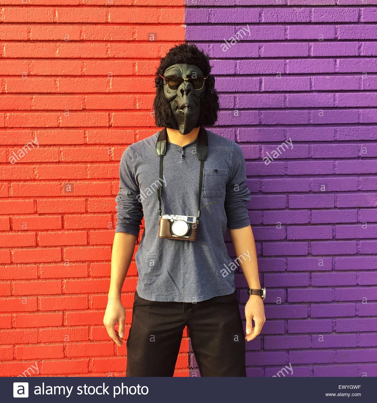 Uomo che indossa una maschera di gorilla con una telecamera intorno al suo collo in piedi contro un variopinto muro Immagini Stock
